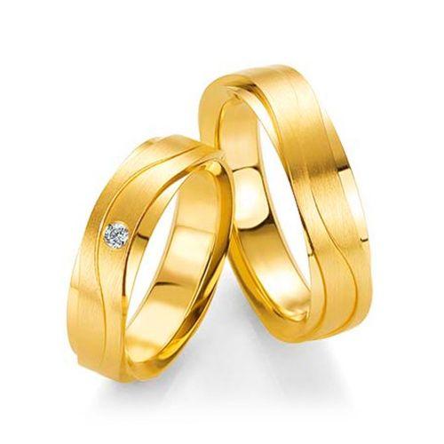 Обручальные кольца с плавными линиями и бриллиантом на кольце невесты